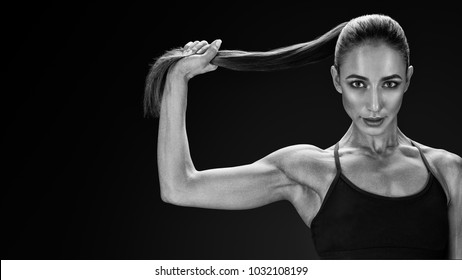 Beautiful young fit sexy woman in sportswear holding her ponytail Strong healthy hair Clipping path Female bodybuilder with power hand confidental looking forward Black and white photo