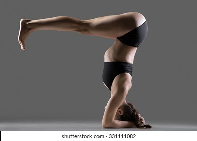 Beautiful young fit woman doing sport exercises, variation of supported headstand asana, salamba sirsasana posture with legs bent at right angle, full length, side view, studio shot on gray background