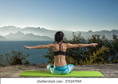 Beautiful young and fit woman exercising yoga at the mediterranean sea in Antalya. Sea and mountains in the background.