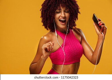 Beautiful young and fit woman in headphones listening music from phone and smiling. Isolated on a yellow background in a pink sportswear