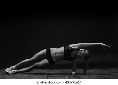 Beautiful young fit woman with muscular body in sportswear doing sport exercise