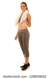 Beautiful young fit woman in shape drinks water after workout isolated over white