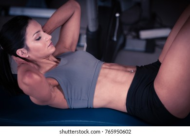 Beautiful young fit woman workout abdominal muscles abs in fitness gym