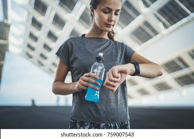 Beautiful young fitness woman checking results after intensive jogging, cofident sporty girl holding energetic drinks and checking her progress on smartwatch touchscreen, healthy lifestyle