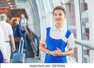 Beautiful young flight attendant in the airport. Unfocused passengers on a background