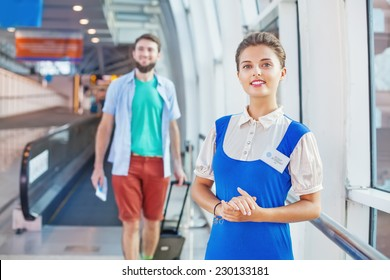 Beautiful young flight attendant in the airport (tourist walking on a background)