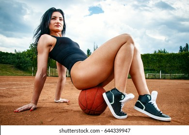 beautiful young free sports sexy girl dressed in bodysuit, sneakers, with a smart ass and long legs, on the sports ground sits on a basketball on a tennis court with a beautiful sky in the background