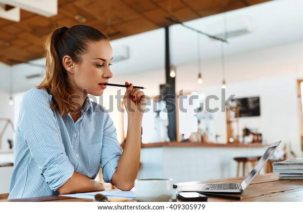 カフェのテーブルに座ったノートパソコンを使う美しい若いフリーランス女性。オンラインで仕事をしたり、ノートを使って勉強や学習をしたりする幸せな笑顔の女の子。フリーランスの仕事、ビジネス・パーソンのコンセプト