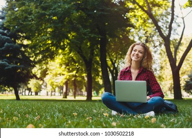 Beautiful young freelancer working on laptop, sitting on the grass in a pleasant atmosphere outdoors in the park. Technology, communication, education and remote working concept, copy space