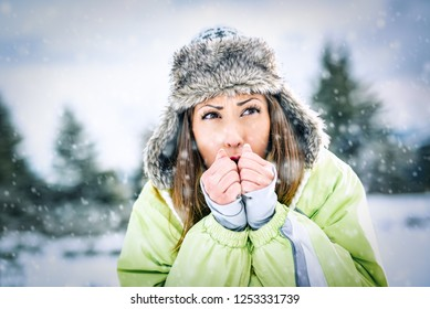 Beautiful young frozen woman skier in winter vacations, standing and looking away.