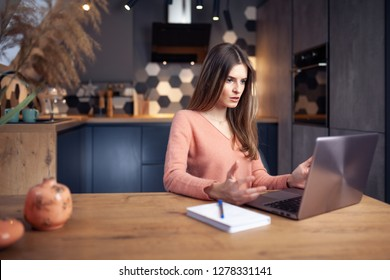 Beautiful young frustrated woman working at home on a laptop, in a warm, cozy environment