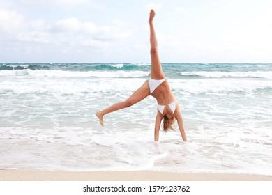 Beautiful young fun woman doing cartwheels in bikini on beach summer holiday, splashing happy energy joy, nature outdoors. Female active vacation acrobatic gymnastics, healthy body leisure lifestyle.