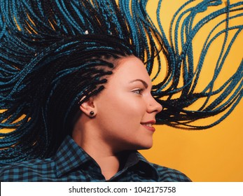 Beautiful young girl with african blue braids. Woman on bright yellow background. Dyed Hair moves. Hipster.