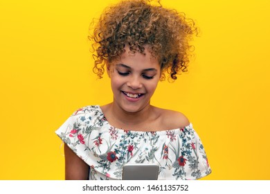 Beautiful young girl with afro hair kid sending a message using smartphone