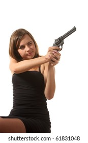 Beautiful young girl is aiming a revolver