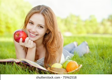 A beautiful young girl with an apple lying on the grass and reading a book beside a basket of fruit is, on a background of green nature