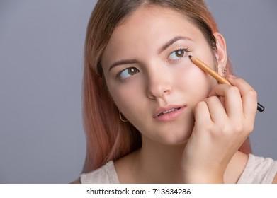 Beautiful young girl applying make up on eyes. Isolated on grey