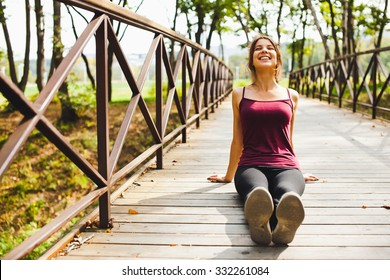 Beautiful young girl athlete on a small bridge in park smiling happy at sunny summer day sitting after run and stretching before training. Getting sunbathes at yoga session. Front view copy space