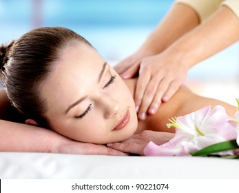 Beautiful young girl with attractive face having a massage for  shoulder on resort - colored background