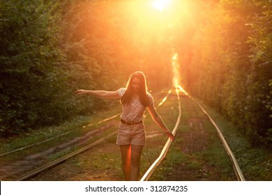 Beautiful young girl balancing, walking on the tram rail in the sunset rays on the summer park alley.