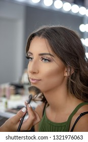 Beautiful young girl in beauty studio, preparing for important event. Professional makeup saloon. Concept: preparation, getting ready, final touch