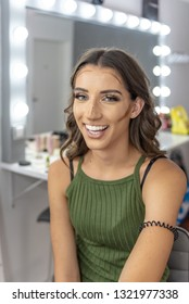 Beautiful young girl in beauty studio, preparing for important event; wearing teeth splinter. Professional makeup saloon. Concept: preparation, getting ready, final touch