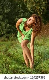Beautiful young girl bent over his leg
