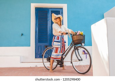 Beautiful young girl with bicycle in front of a blue house wearing colorful fashion dress with large hat in Sunny summer, in Ponza island Italy