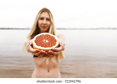 Beautiful young girl in bikini gives Sicilian grapefruit on a background of nature. Close up
