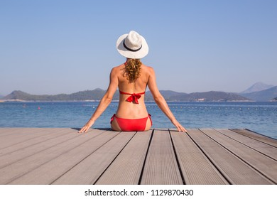 Beautiful young girl in bikini sits in the beach of a southern sea resort