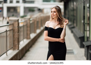 beautiful young girl in black dress walking the streets of the city, the woman is resting outdoors, street fashion. urban lifestyle.