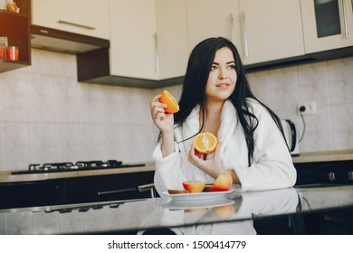 beautiful young girl with black hair dark and white robe sitting at home in the kitchen at the table and eating an orange and apple