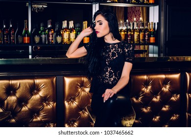 Beautiful young girl in black pensively sits at the bar counter