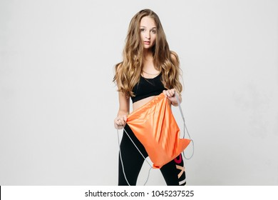 Beautiful young girl in black sportswear looking at camera and posing.  Sporty pretty model with wavy hear standing in studio, holding orange rucksack in hands. Concept of sports, fitness.