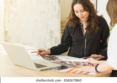 Beautiful young girl in a black sweater discusses a business project. Empty space on the left.