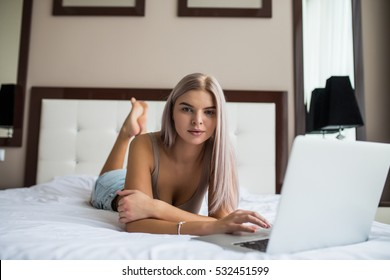 Beautiful young girl in black underwear with laptop in bed at home