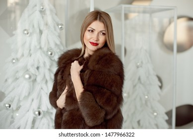 Beautiful young girl with blond hair and bright makeup in a long mink coat on a background of white Christmas tree and lights.