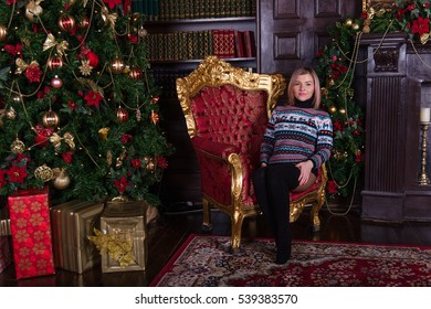 Beautiful young girl with blond hair in a sweater sits on a chair in front of the Christmas tree