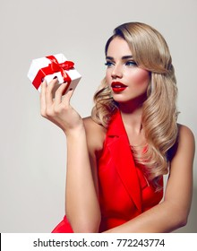 A beautiful young girl with blond hair and red lips is holding a white gift box with a red ribbon.