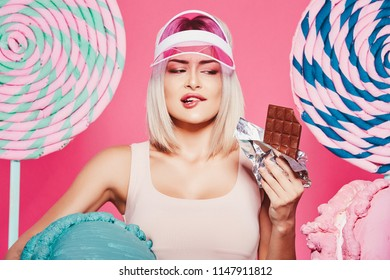 Beautiful young girl with blonde hair wearing top and skirt standing with huge sweet lollypops at pink background, candy lover, portrait, eating chocolate.