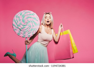 Beautiful young girl with blonde hair wearing top and skirt standing with huge sweet lollypops and holding colorful shopping bags at pink background, candy lover, portrait.