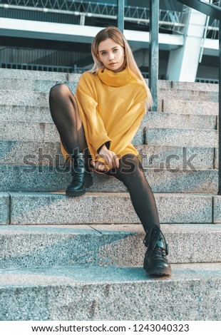 013eb4a65b A beautiful young girl blonde walks through the streets of the city. She is  wearing