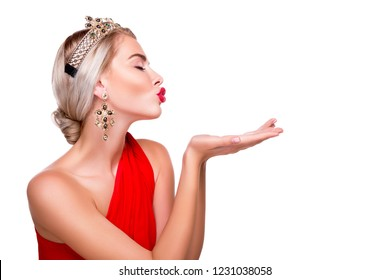 beautiful young girl blowing a kiss over her empty palm with closed eyes for joy and delight. model wearing exquisite jewelry-earrings chairs and a crown, a woman in profile is isolated on background