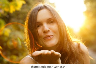 Beautiful young girl blowing a kiss at sunset