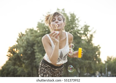 Beautiful young girl blowing soap bubbles