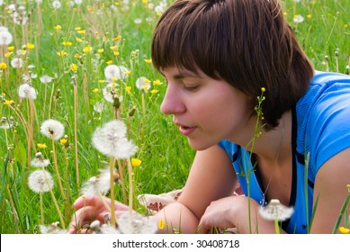 Beautiful, young girl blows on a dandelion