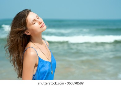 Beautiful young girl in a blue dress against the sea