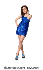 Beautiful young girl in a blue dress with sequins posing in studio isolated on white