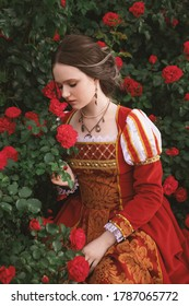 beautiful young girl with blue eyes in a dress in a medieval style is sitting in the garden with red roses, fantasy princess