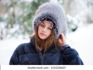Beautiful young girl in a blue fur hat and fur coat. Portrait Fashion, beauty, warm clothes, fur, headdress, outerwear, winter park outdoors